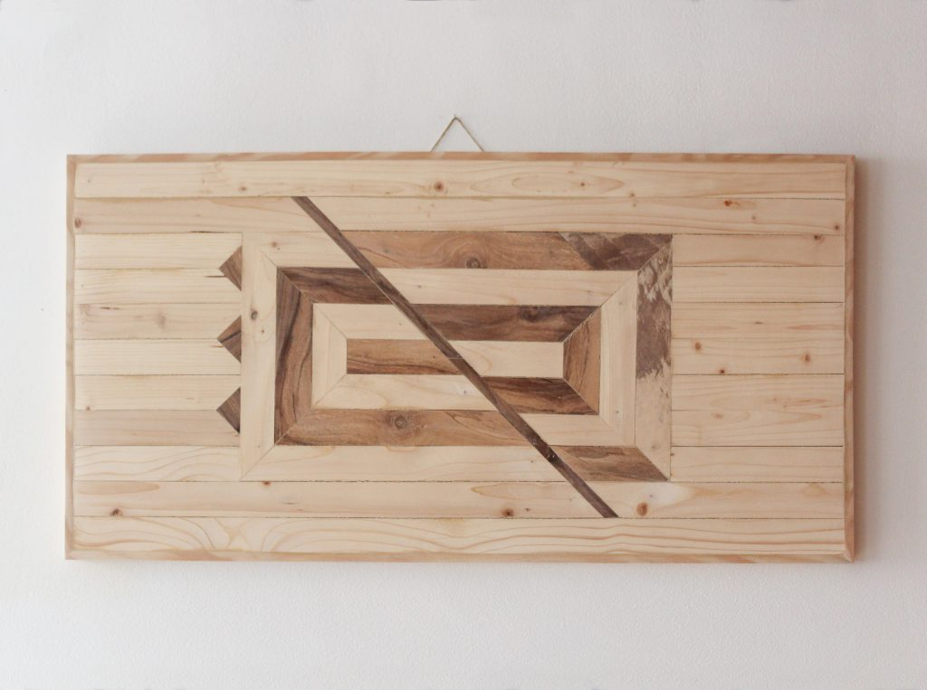 Wooden art piece to be hung on the wall. The design represents geometrically mirrors. We can see ourselves through the interaction with people, who are our mirrors.